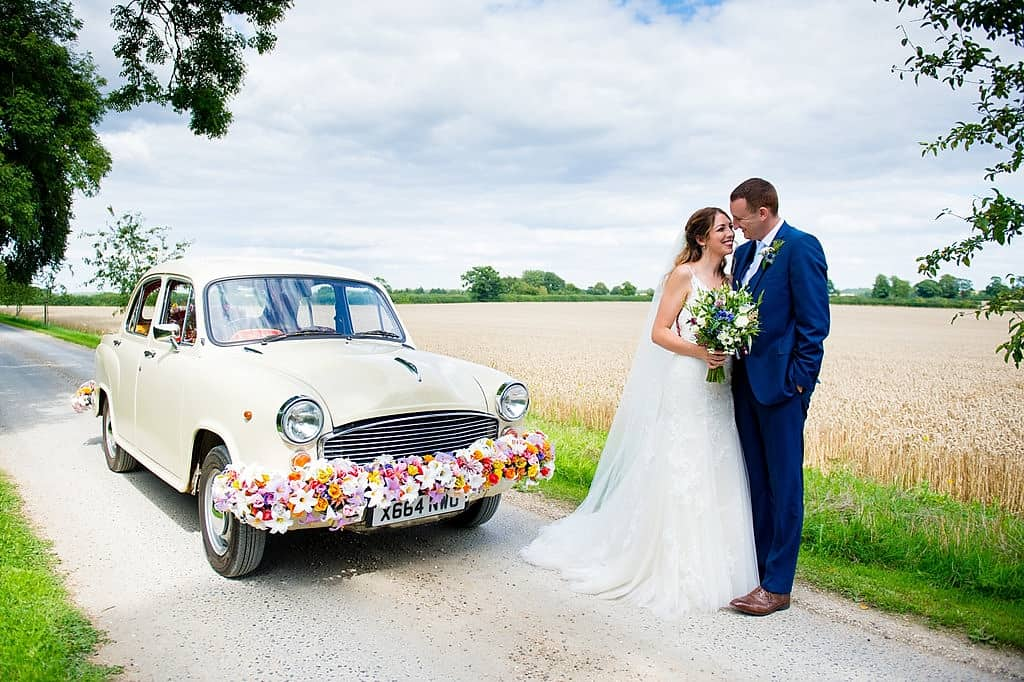 Indian wedding car and bride and groom at