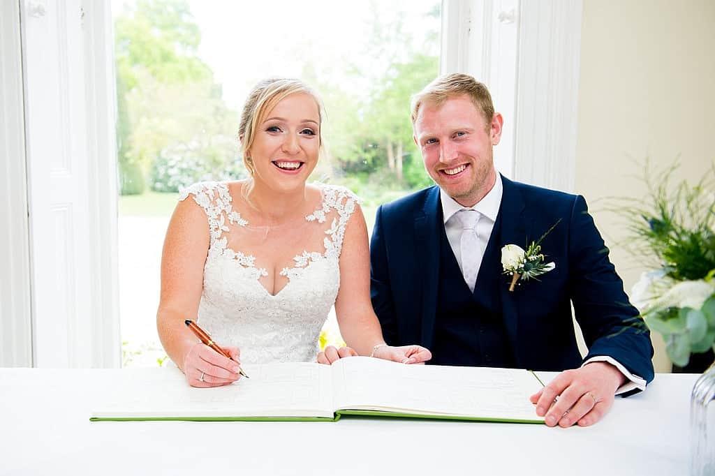 Bride and groom signing wedding register