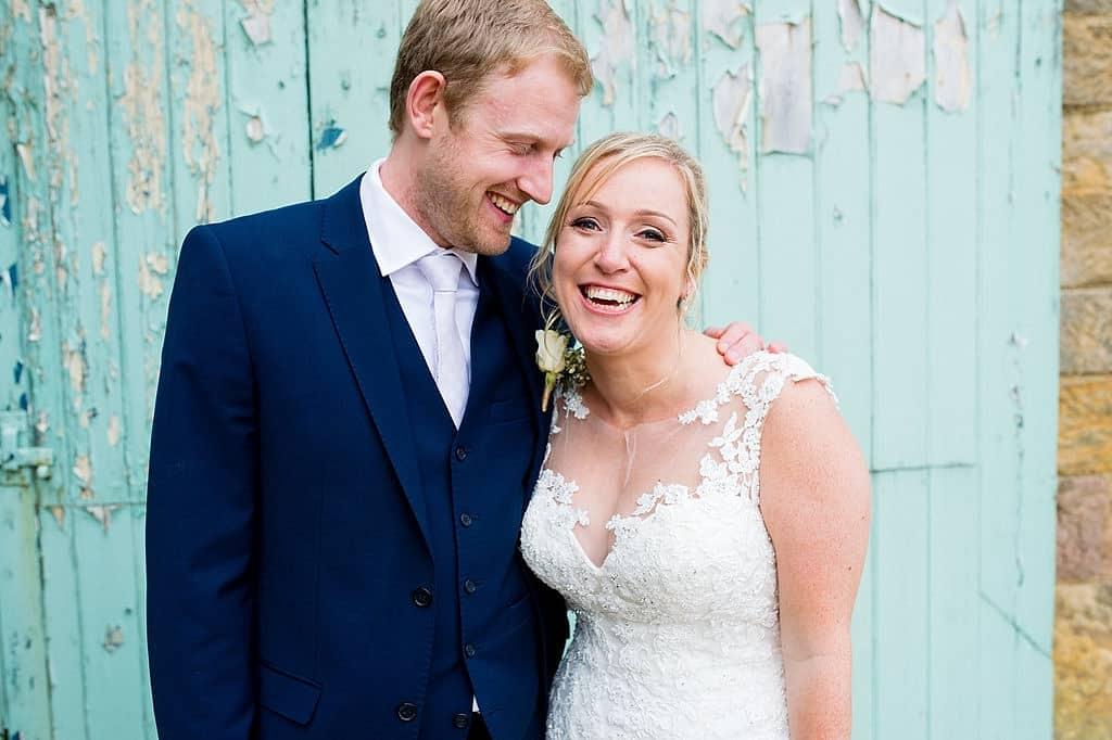 Smiling bride and groom against barn doors