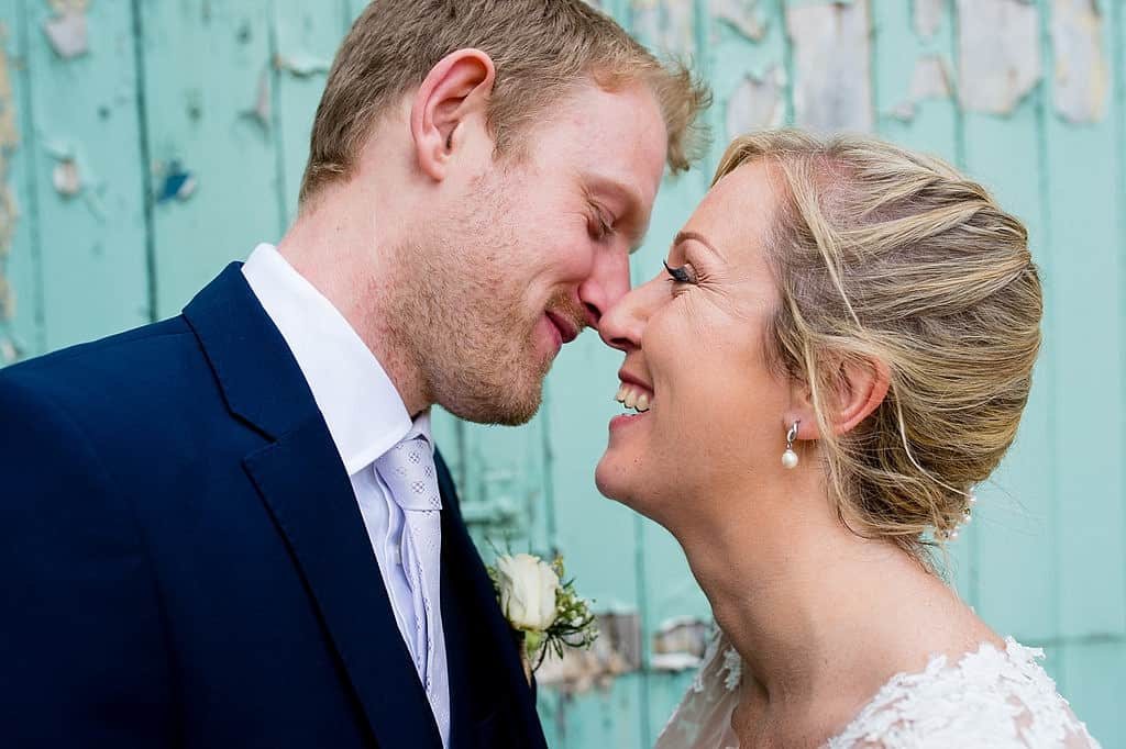 Smiling bride and groom against turquoise barn doors