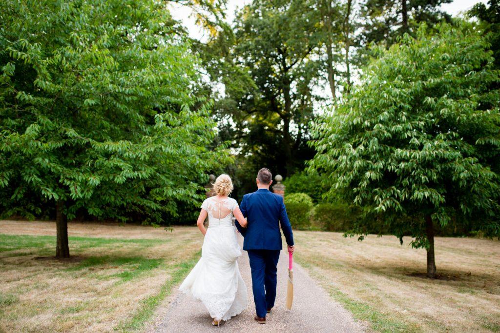 Bride and Groom walking with cricket bat