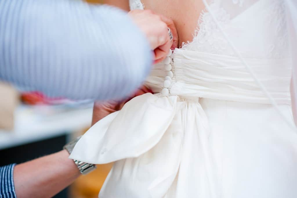The wedding dress being buttoned
