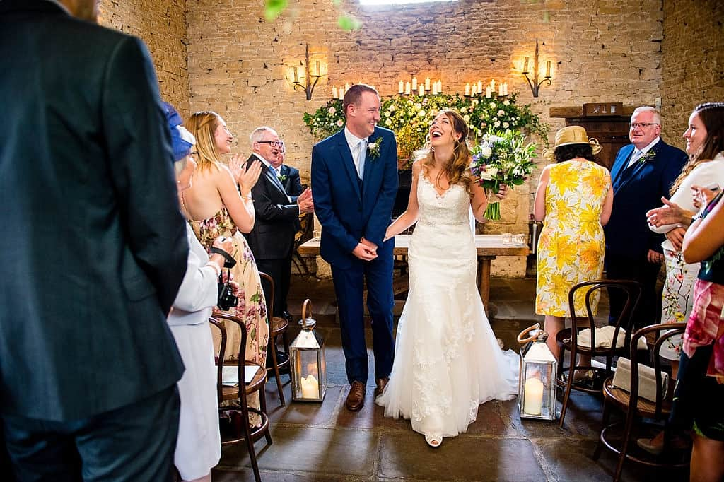 Bride and Groom walking down the aisle at Cripps Barn