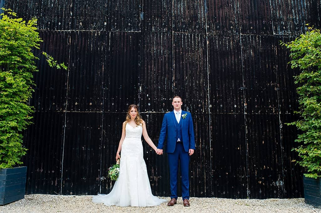Bride and groom in front of black barn at Cripps Barn