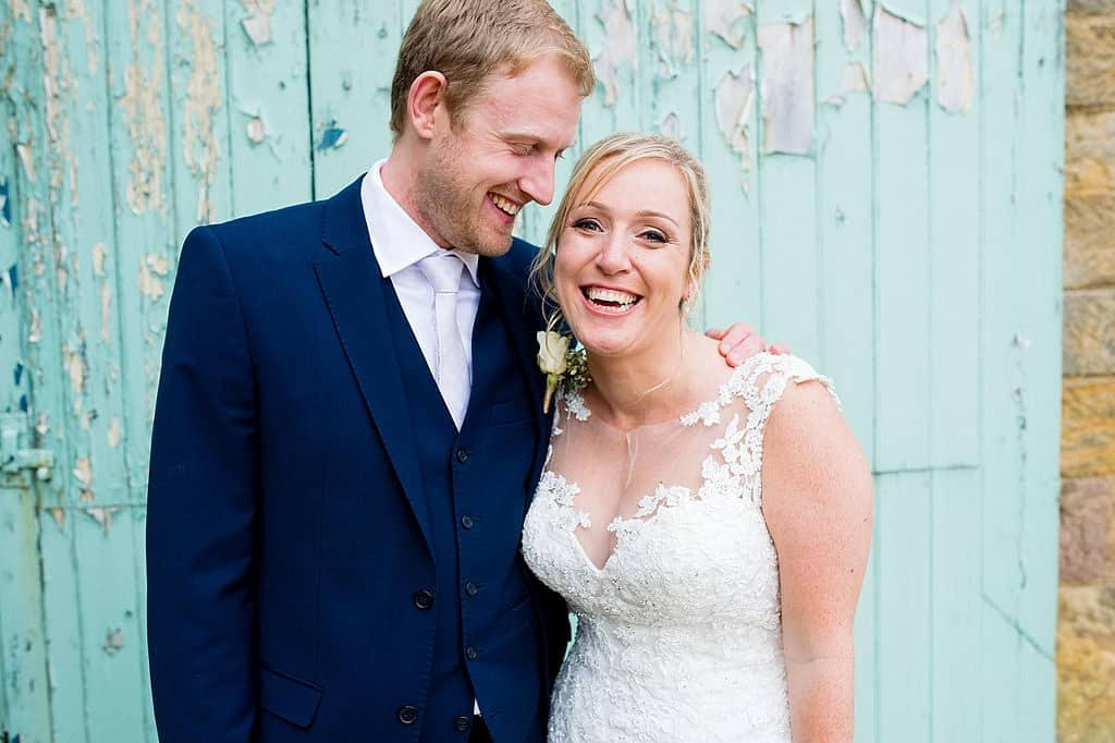 Smiling bride and groom against barn doors
