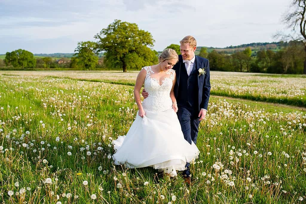 Bride and groom walking in dandelion field