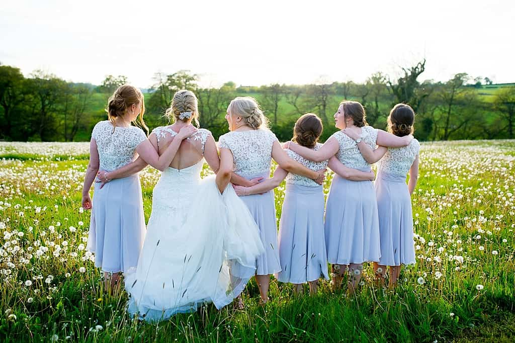 Bride and bridesmaids in dandelion field