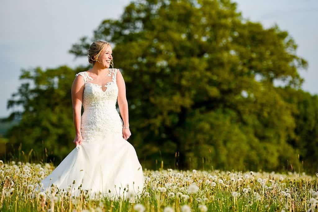 Bride in Dandelion field at Shottle Hall wedding