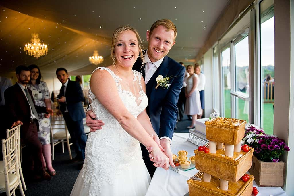 Bride and groom cutting pork pie wedding cake