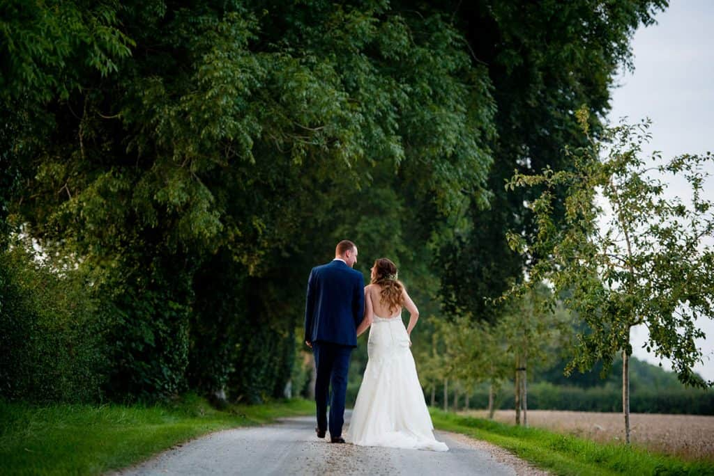 Bride and groom walk off down the road
