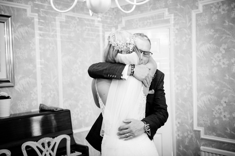 Father of the bride hugging bride